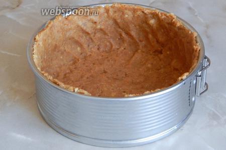 Берём разъёмную форму (моя 18 см) и руками выкладываем в неё основу из печенья. Делаем бортики, просто прижимая тесто.