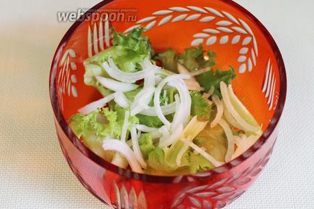 Разбросать лук поверх листьев салата.