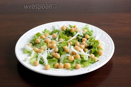 На тарелку выложить листья салата, немного разного лука и кинзы. Рассыпать часть гороха нут.