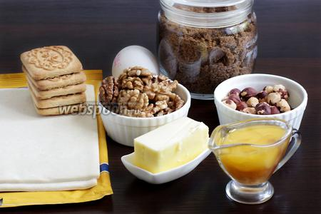 Для приготовления ореховых хрустиков возьмём тесто слоёное, масло сливочное, мёд, орехи грецкие и фундук, белок яйца, коричневый сахар, печенье.