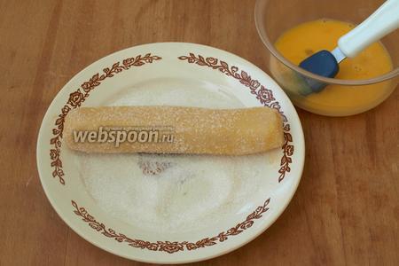 Взбиваем вилкой яйцо. Достав колбаски из холодильника, смазываем каждую яйцом и обваливаем в сахаре.