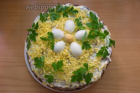 Верхнюю часть ореховой массой не смазывать. Смажьте её просто майонезом. Мы откладывали 3 желтка. Натрите их на мелкой тёрке и посыпьте ими торт. Дальше торт следует украсить по вкусу. Я использую отварные перепелиные яйца и зелень. Через 2 часа можно тортик подавать к столу. А до этого времени торту следует дать пропитаться в холодильнике.