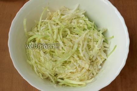 Тонко нашинковать капусту. Выложить её в глубокий салатник.