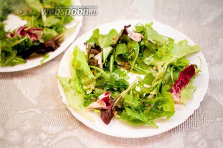 Промытые и обсушенные салатные листья смешать с заправкой и выложить на тарелки, оставляя место посередине для груш.