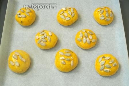 Застелить пергаментом противень и выложить на него булочки. Смазать их желтком и посыпать оставшимися семечками.