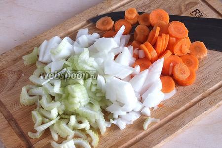 Очистите и нарежьте кусочками лук, морковь и сельдерей.