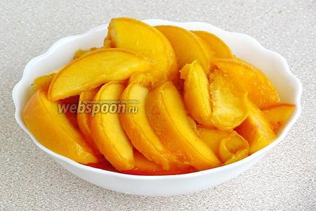 Персики выложить на дуршлаг, дать стечь жидкости и нарезать мякоть дольками.