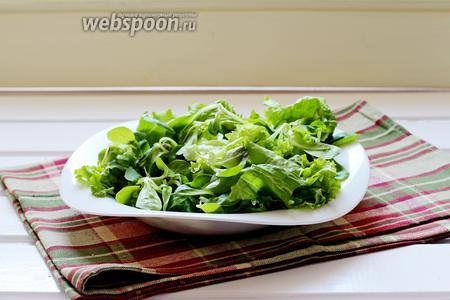 Выложить на тарелку подготовленные листья салата.