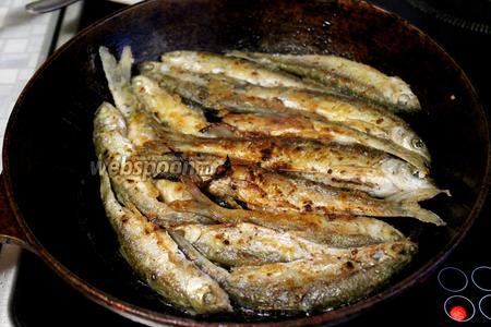 Переворачиваем, словно блин: подхватываем лопаточкой и всю рыбу одновременно переворачиваем. Если с краю 1-2 рыбки с первого раза отвалятся от общего «блина» — это не страшно, просто переверните их отдельно. Зажарить вторую сторону до румяности и — рыбка готова! Хрустящая, с пылу-с жару, подавать с салатом из свежих овощей.