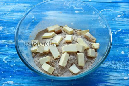 Смешать все сухие ингредиенты (2 вида муки, сахар, соль, цедра) добавить масло (порезанное кубиком).