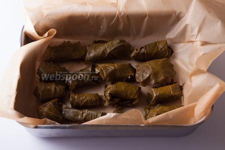Конвертики из листьев с сыром выкладываем на слой кондитерской бумаги.