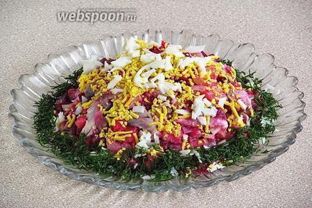 Посыпать салат измельчёнными яйцами и украсить рубленым укропом.