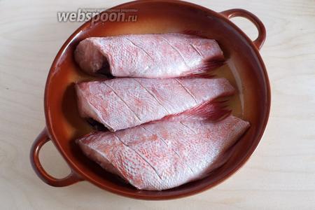 Разогрейте духовку да 190°С. Смажьте форму 2 ст. л. оливкового масла. На каждой рыбе сделайте по 3 тонких глубоких разреза, с каждой стороны тушки. Выложите окуней в форму.