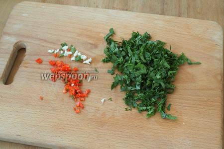 Нарезать мелко петрушку, измельчить горький перец и чеснок.