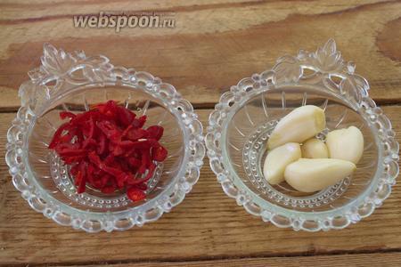 Красный острый перец очистите от семян. Нарежьте мелко. Чеснок очистите. При работе с перцем лучше использовать перчатки. Очень жжётся.