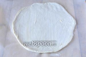 Тесто раскатываем толщиной примерно 1 сантиметр, выкладываем тесто на пергаментную бумагу, придаём круглую форму. Смазываем тесто майонезом.
