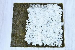 Кладём на него тонким слоем рис. Взбрызгиваем рисовым уксусом.