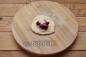 1 шарик теста раскатайте в пласт. Выложите несколько ягод вишни. Добавьте 1 чайную ложку сахара. Соберите края, сформировав пирожок.