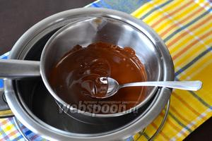 Духовку включить разогреваться на 180°С. Шоколад поломать на куски и растопить на водяной бане. Как только шоколад полностью растает, отставить в сторону на 10 минут.