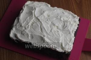 Взбить сливки с сахарной пудрой до устойчивых пиков и выложить на пирог. Поверхность разровнять и посыпать миндальными лепестками.