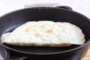 Обжарить лепёшки с двух сторон на сухой сковороде до румяных подпалинок. Тесто начинает слоиться ещё на сковородке, а лепёшки могут надуваться, если не выгнали весь воздух при лепке. Готовые лепёшки сложить на большое блюдо и накрыть тарелкой, пока жарятся остальные.