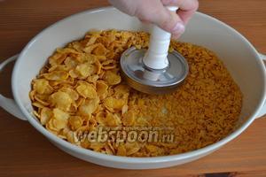 Кукурузные хлопья выложить в миску с высокими бортиками и поломать помельче.