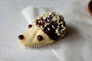 Затем присыпаем шоколад рубленым орехом и кунжутом. Делаем глазки и носик шоколадом.