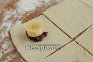 На середину каждого квадратика положить 1 ч. л. шоколадной пасты и 1 кружочек банана.
