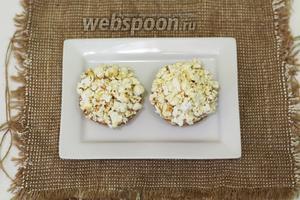 На водяной бане растапливаем белый шоколад, остужаем. Когда шоколадная масса немного загустеет, смазываем верх капкейка и обильно посыпаем немного измельчённым попкорном. Оставляем немного застыть. Параллельно растапливаем чёрный шоколад. С помощью шприца выдавливаем личико и рожки на лист пергамента и даём остыть, или можно отправить в морозилку на 10-15 минут.