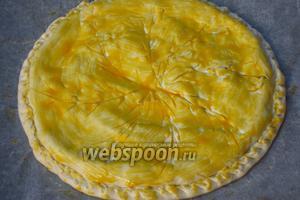 На поверхности острым ножом сделать надрезы в виде спиц колеса. Смазать поверхность пирога оставшимся желтком и выпекать в разогретой до 180°С духовке 20 минут.