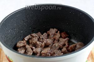 Обжарить мясо в растительном масле до румяной корочки.  Масло должно быть хорошо разогрето, чтобы мясо не выделяло сок, а корочка схватывалась сразу.
