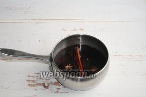В кастрюлю вылить вино, сок апельсина и добавить все специи, сахар. Поставить варить на средний огонь.