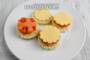 Теперь подготовим основу канапе. На хлебец выложить дольку сыра. Сверху выложить кружок помидора. И снова накрыть помидор долькой сыра.