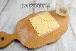Развернуть упаковку, не снимая её, снизу ломтика сыра. С помощью вырубки нарезать сыр кругами.