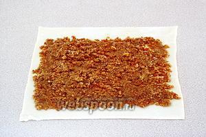 На размороженный пласт слоёного теста нанести слой овсяной массы.