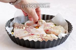 Сверху разложить кусочки маринованной рыбы в чесноке.