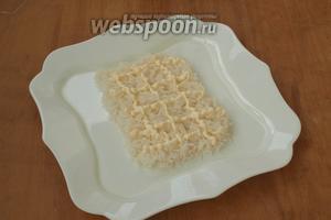 Рис остудить и выложить на блюдо в форме прямоугольника. Нанести майонезную сеточку.