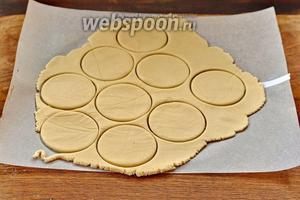 Вырезать из теста круглые коржики с помощью специальной формы для вырезания или тонкого стакана.