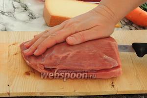 Филе придавим одной рукой к разделочной доске, а другой рукой разрежем филе по длине куска, оставляя целым боковой край, около 1 см. Нож должен быть острым.