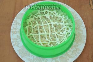 Картофель натереть на тёрке. На круглое блюдо положить кольцо по центру. Выложить картофель первым слоем и нанести майонезную сетку.