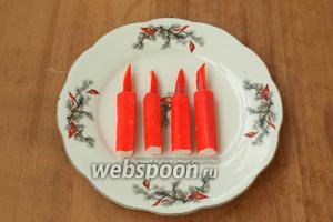 Отложенные крабовые палочки разрезать пополам. Из красного перца вырезать «пламя» для свечек. В каждой крабовой палочке сверху сделать небольшое отверстие и вставить в него перец. Получатся свечки.