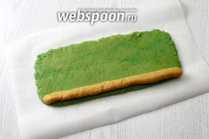 Из половины белого теста раскатайте колбаску длиной 25 см и выложите скраю вдоль зеленого пласта.