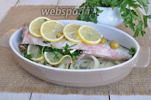 Выложить на лук начинённую зеленью рыбу. На рыбу положить нарезанные оливки и полить вином. Сверху выложить лимон и поставить запекать при 200°С на 25-30 минут.