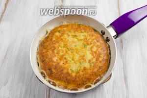 Накрыть сковороду тарелкой подходящего диаметра. Перевернуть омлет на тарелку. Перевернутый омлет выложить обратной стороной на сковороду. Жарить в течение 5 минут.