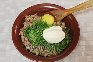 К охлаждённому фаршу добавить зелень, сметану, 1 яйцо.