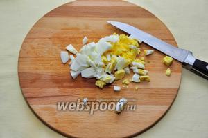 Вареные яйца очистим и нарежем небольшими кубиками.