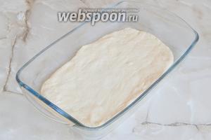 Растопленным маслом смазываем форму. Кладём первый пласт теста.