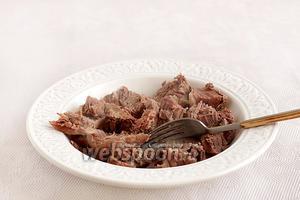 Как только мясо стало мягким, достать его на тарелку, убрать кости и нарезать кусочками.