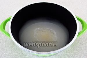 Сахар высыпать в кастрюлю с толстым дном, залить горячей водой и довести до кипения.