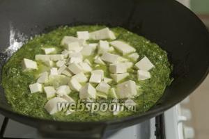 Добавляем кусочки сыра в пряный шпинатно-молочный соус.